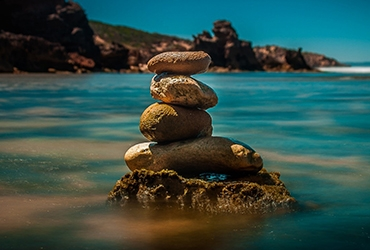 Four Stacked Stones on Ocean Water