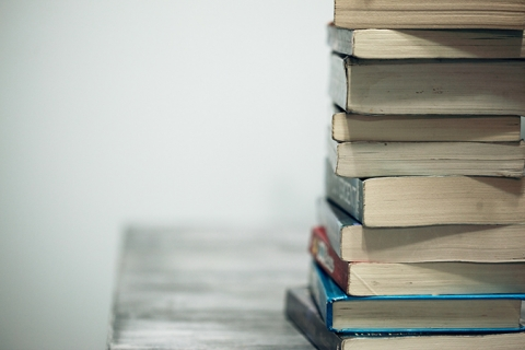 Image of stack of books on desk surface close to the edge.