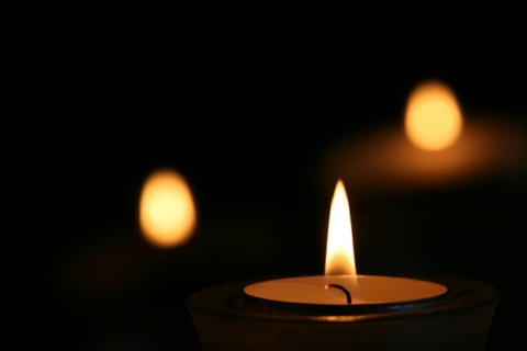 Close up of candle light with two fuzzy candle lights in the dark background.