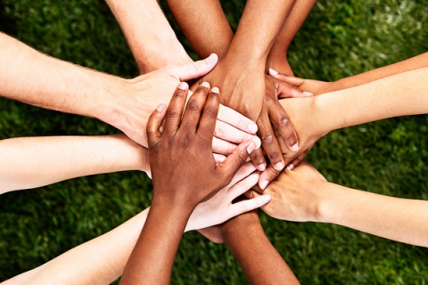 Hands of various skin tones put on top of each other in a circle.