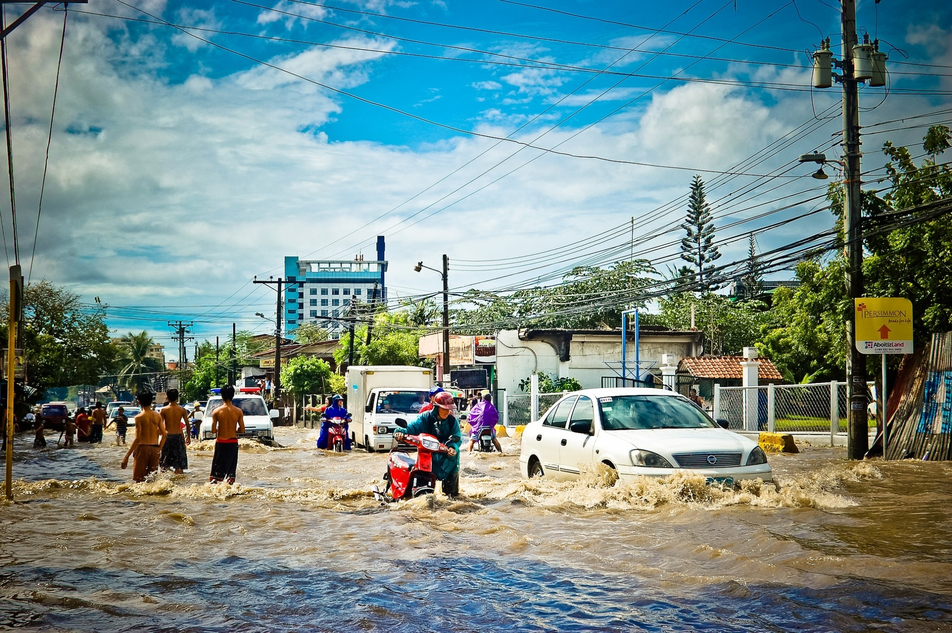 People and cars in a flooded street.