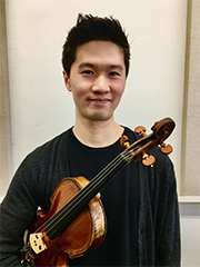 Aaron Chan holding violin