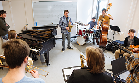 Professor Remi Bolduc playing saxophone with class