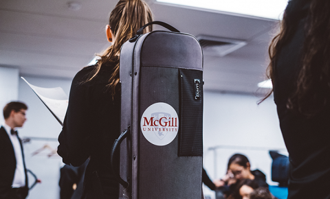 Musician carrying instrument case with schulich school of music logo