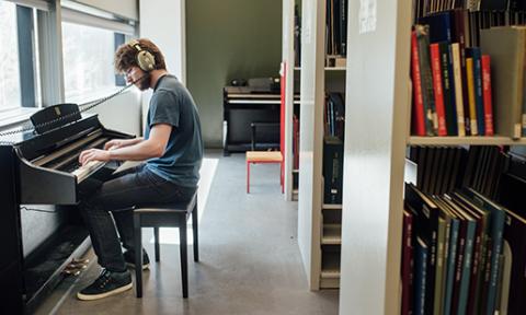 Student wearing headphones practices piano