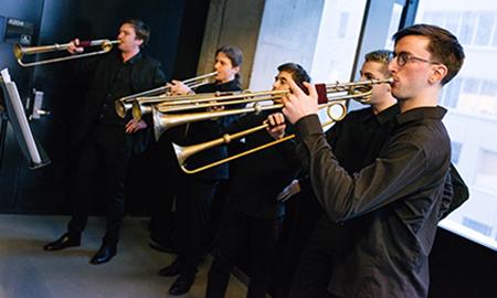 brass musicians standing in a line