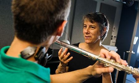 Professor show proper technique to flute student