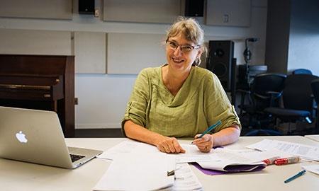 Professor sitting at desk holding pen