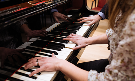 hands of student playing piano