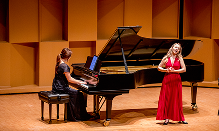 girl in red dress and pianist