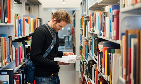 Student looks through book in library