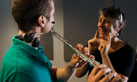 Professor demonstrates proper technique to flute student
