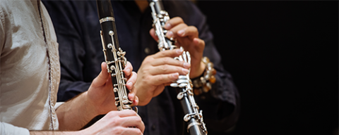 two students playing clarinet