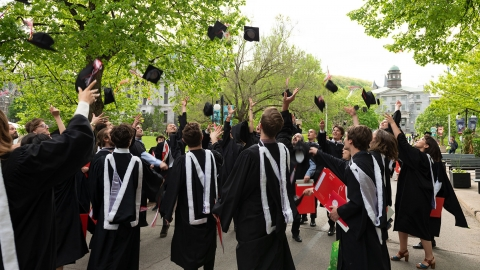 Students toss their mortar boards in the air shortly after receiving their degrees