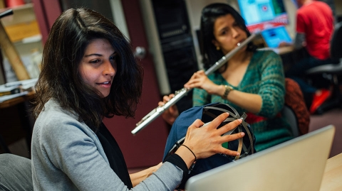 Music students practice while looking at laptop screen