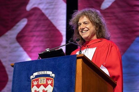 Pat Metheny standing at podium for convocation address to students