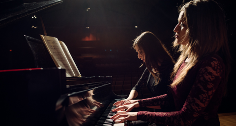 Two female pianists playing a piano