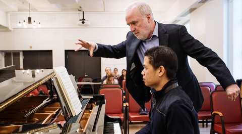 Michael McMahon oversees student on piano