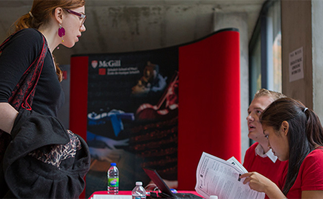 prospective student is greeted at welcome table during Open House