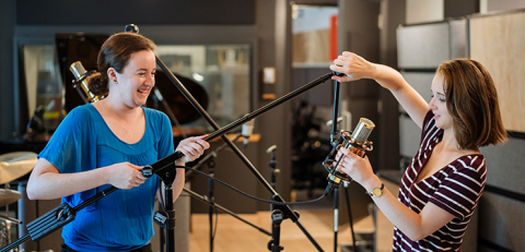 sound engineers playfully holding microphone