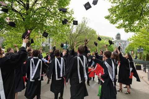 recent graduates toss mortar boards in the air