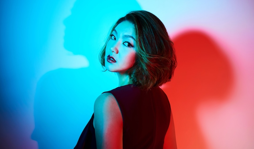 Jinjoo Cho in front of a red and blue lit background