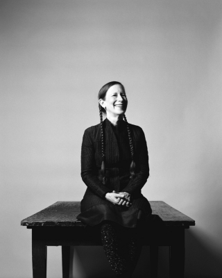 Meredith Monk sitting on a bench while smiling.