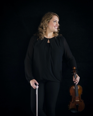 Clarissa Klopoushak holding her violin and bow
