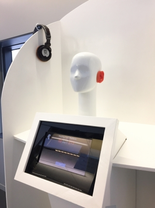 A white mannequin head with orange silicon ears used to test noise levels.