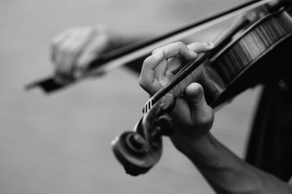 Black and white image of a person playing a violin