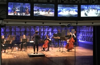 Photo of musicians, including cello, double bass, and percussion being led by a conductor. They are seen through a recording studio window with televisions capturing various angles of the recording session.