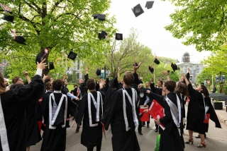 Graduates throwing this caps in the air outside McGill's convocation tent
