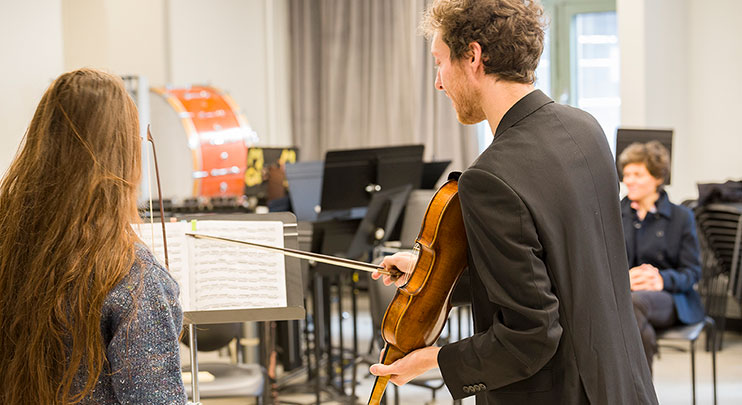 Music professor assisting student