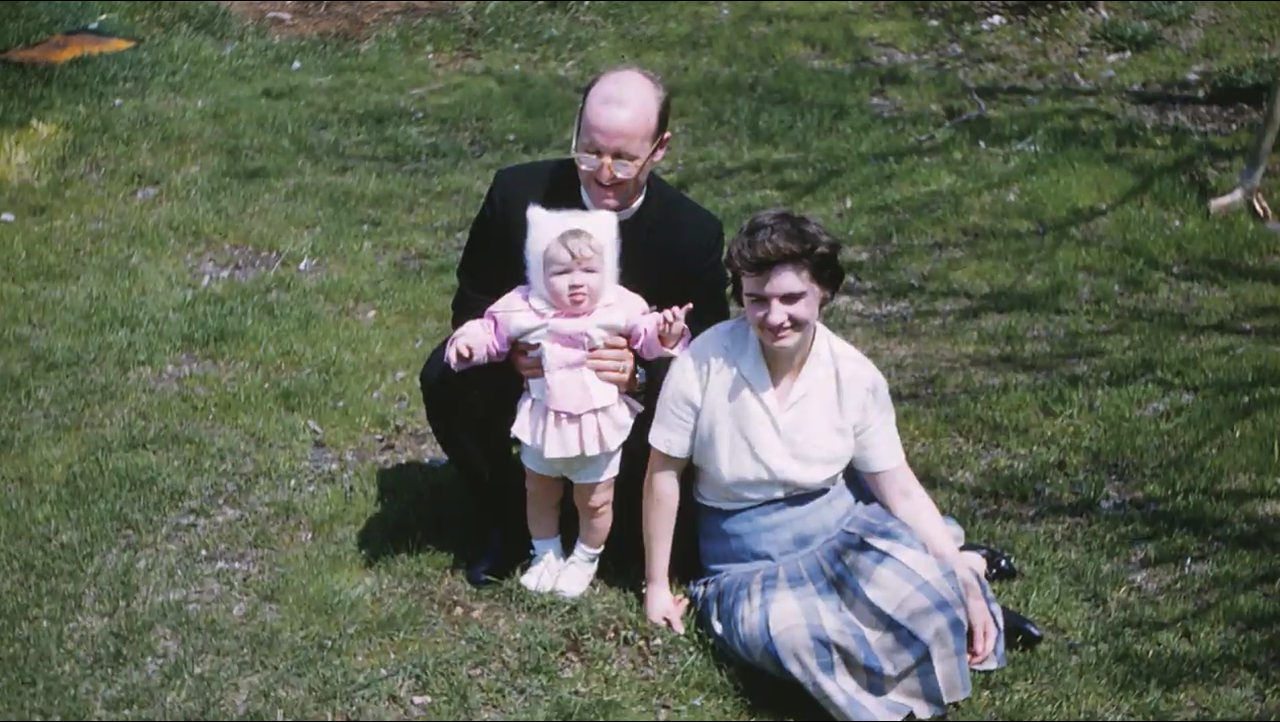 Two parents on lawn holding infant Angela Genge in costume