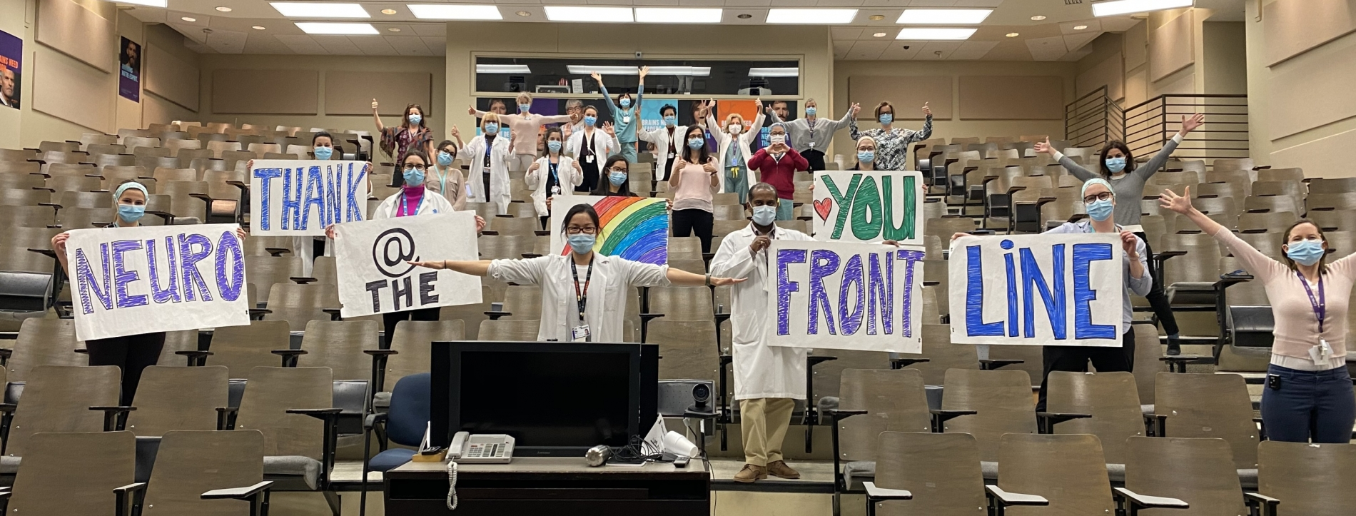 """The Neuro Frontline Staff in the Jeanne Timmins Ampitheatre holding up """"Thank You"""" signs"""