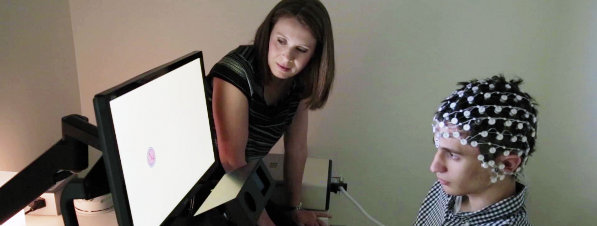 Autism researcher and patient looking at a screen.