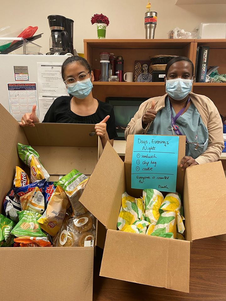 Two members of our Neuro Staff present boxes filled with Subway sandwiches and other goods.