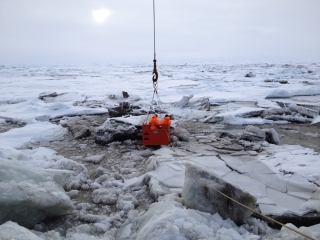 This image shows sediment-rich sea ice in the Transpolar Drift Stream. A crane lowers two researchers from the decks of the icebreaker RV Polarstern to the surface of the ice to collect samples. Photo Credit: R. Stein, Alfred Wegener Institute