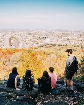 A group of people overlooking the Montreal skyline from Mount-Royal.