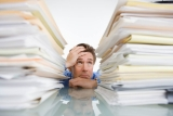 A man feeling stressed behind a mountain of work