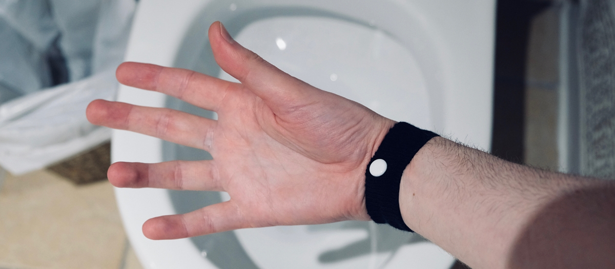 A photo of someone's hand wearing a black fabric wrist band with a small white button on it on the inside of the wrist, hand held above a toilet