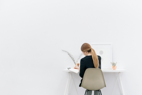View of a woman's back as she sits working at a desk