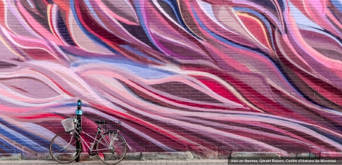 Image of bicycle against wall with brightly painted swirls