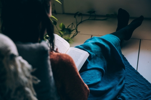 Woman sits on floor reading