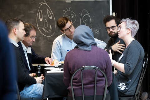 Photo of six people chatting around a table.