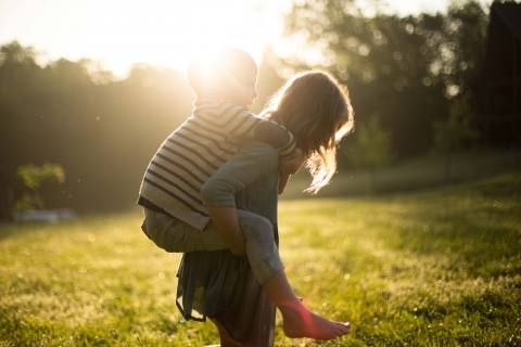 Woman carrying a child on her back in a sunny field