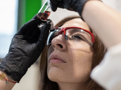 Lab technician holding up a test tube with a red liquid to her eye