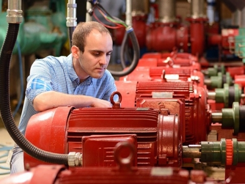 A researcher working on industrial red machinery