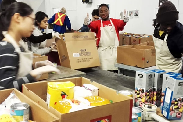 Students help package and distribute food at Moisson Montreal