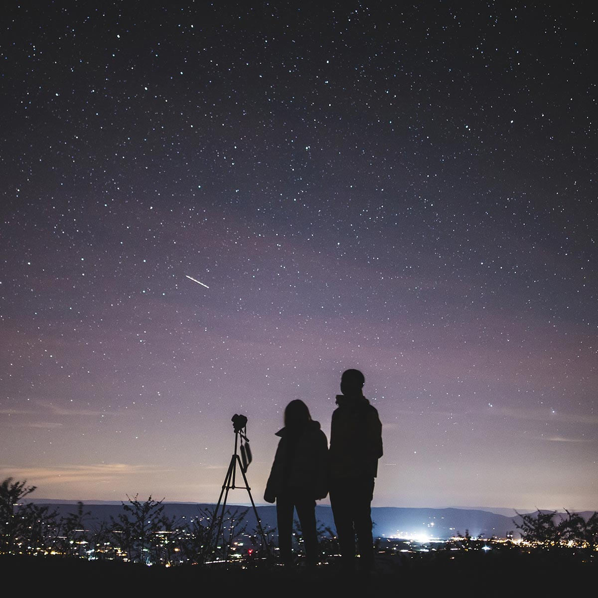 Two people with a telescope looking at the night sky